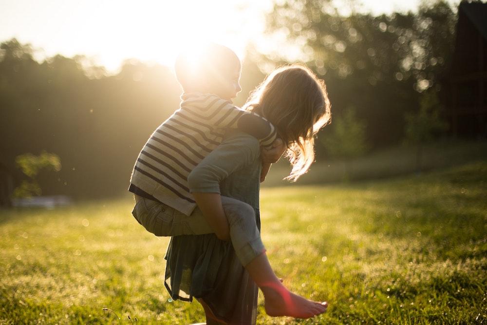 little girl giving little boy piggy back ride