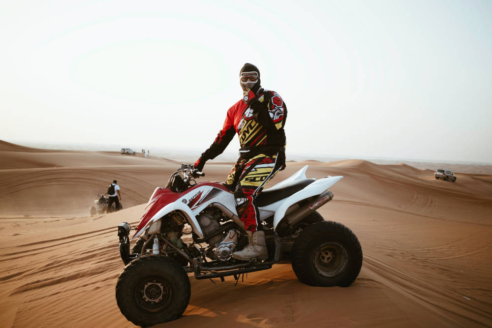 red and white atv on sand dunes