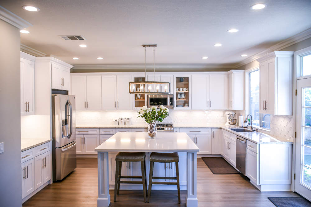 white kitchen with island and recessed lighting