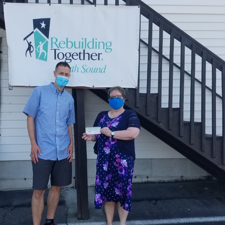 Ryan Stueber from PNW Insurance Group dropping off donation check to RebuildingTogether South Sound
