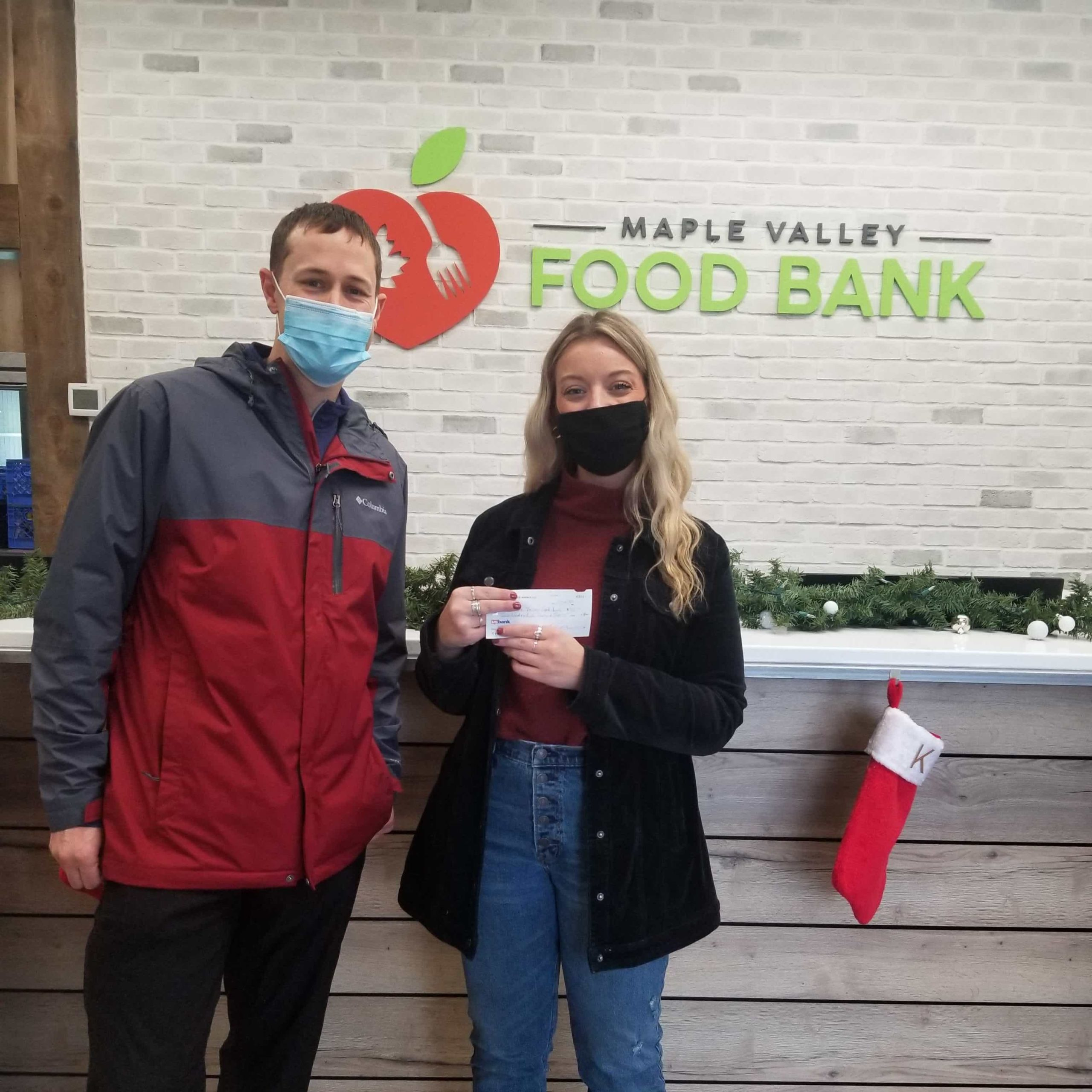Ryan Stueber from PNW Insurance Group dropping off donation check to Maple Valley Food Bank