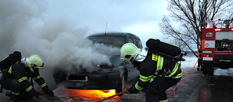 fire fighters extinguishing car on fire